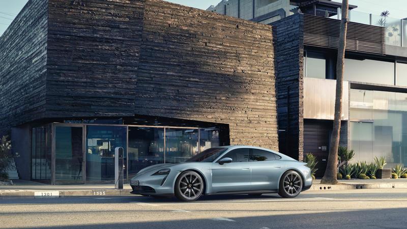 Frozen blue metallic Porsche Taycan car parked in front of a building