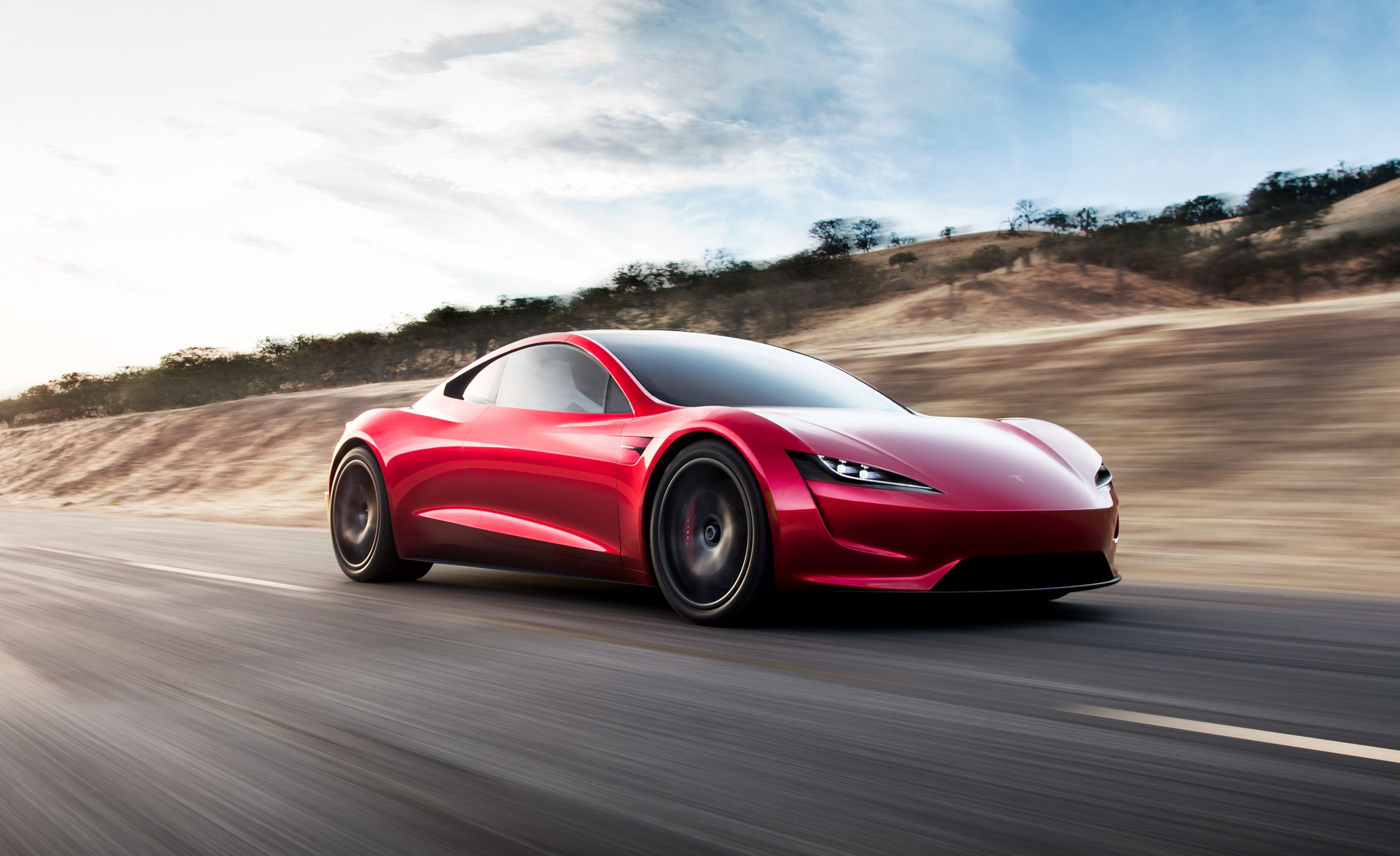 A red Tesla Roadster driving on the road